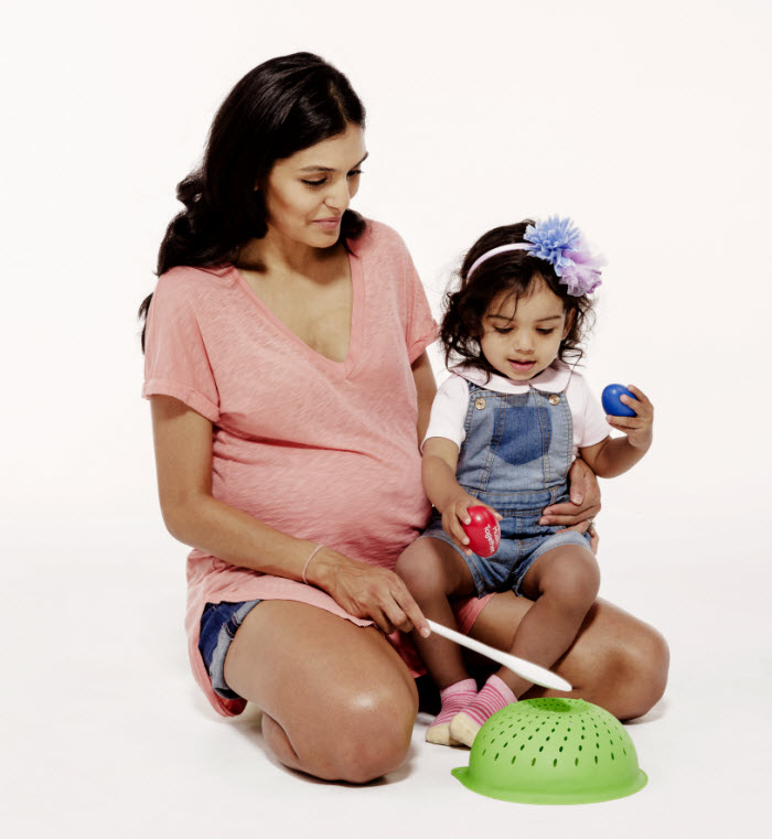 Pregnant mom with toddler daughter, playing kitchen instruments and shakers
